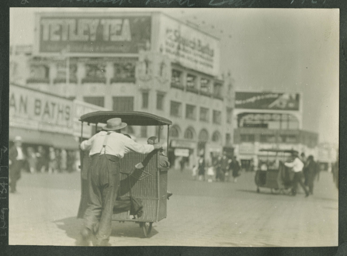 "Pushing a wicker ""taxi"" in Coney Island, New York."