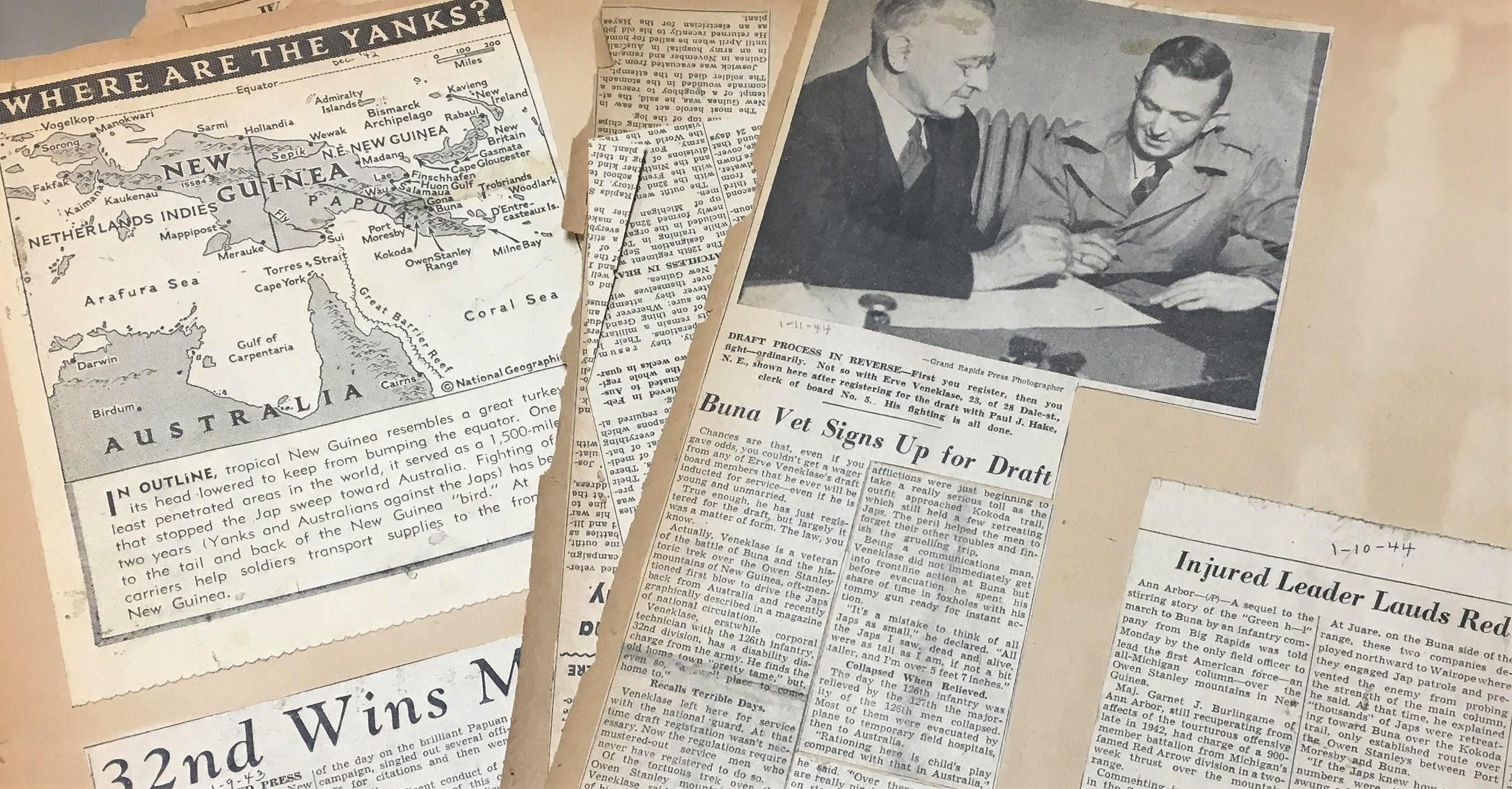 Close-up view of deteriorating newspaper scrapbooks from World War II.