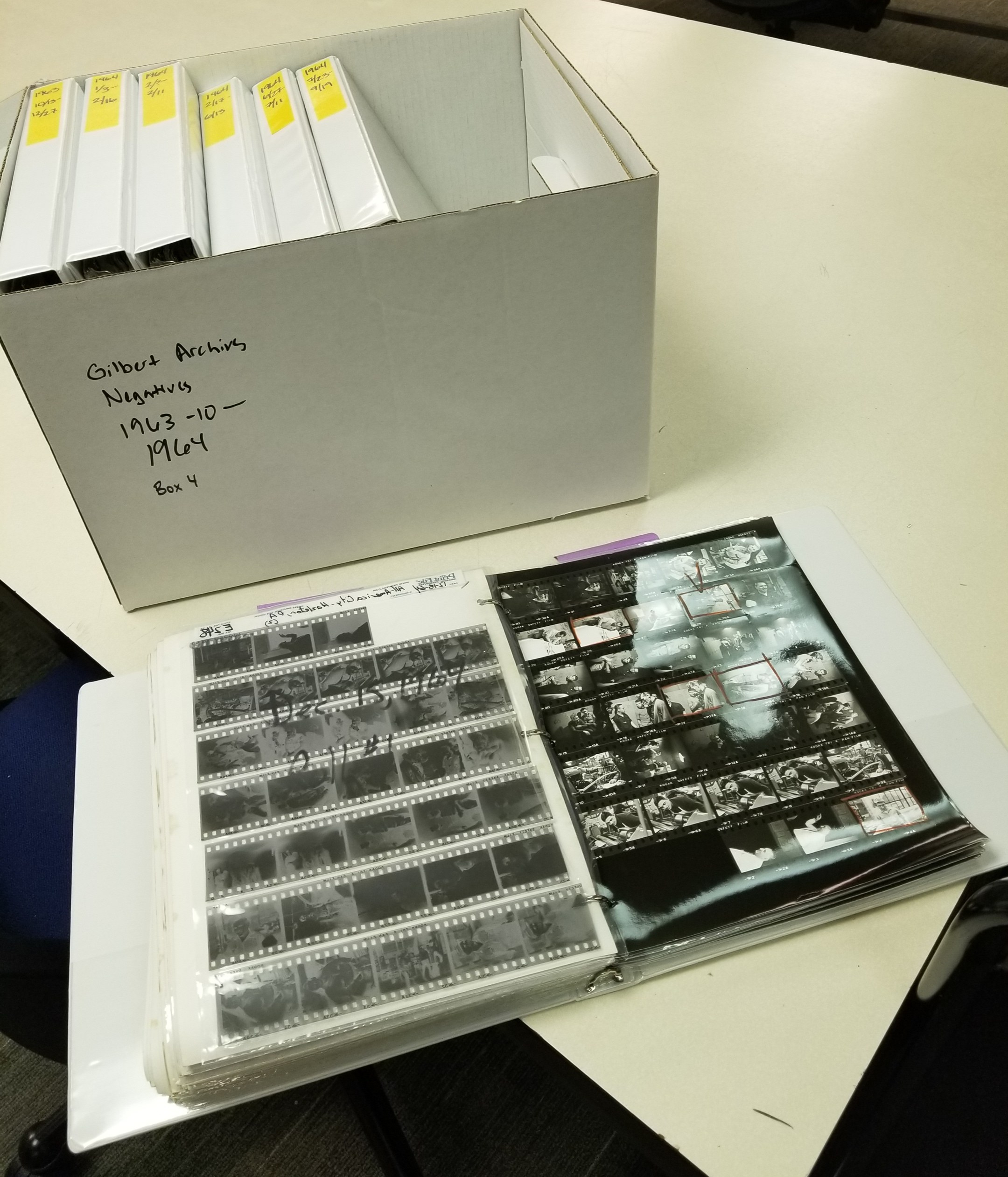 A binder full of 35mm photo negatives and contact sheets sits in front of a box full of binders