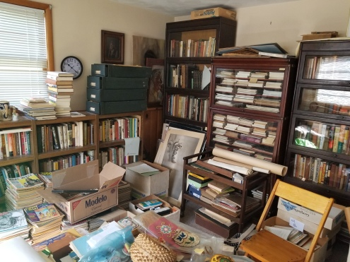 Photo of a room full of bookcases packed with books, newspapers, magazines, index files, and other materials