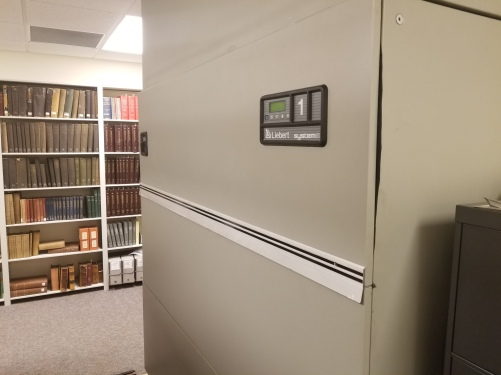 A large gray Leibert HVAC unit situated in the archival storage area
