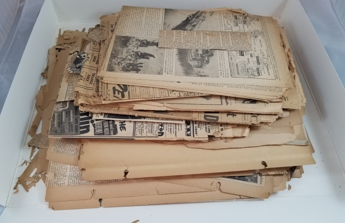 A box contains a stack of yellowed and crumbling newspapers and scrapbook pages.