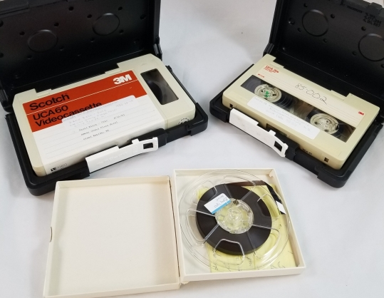 Two U-Matic video cassettes and one small reel-to-reel audio tape