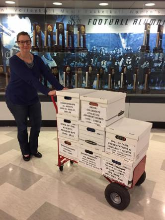 An archivist standing with a cart of record boxes in front of a trophy case
