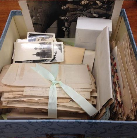 A small blue box is filled with bundles of letters tied with ribbons and stacks of black and white photographs